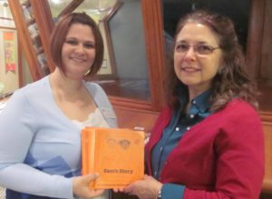 Club President Amy Luckiewicz presents Library Dorector Sharon Gilley with 5 copies of Sam's Story.