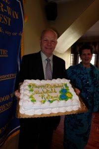 Past President Tom Stapleton holding the club birthday cake.