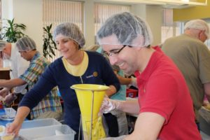 Wakefield Rotarian Mario Portillo packages meals alongside Amesbury Rotarian Terri Doerfler.